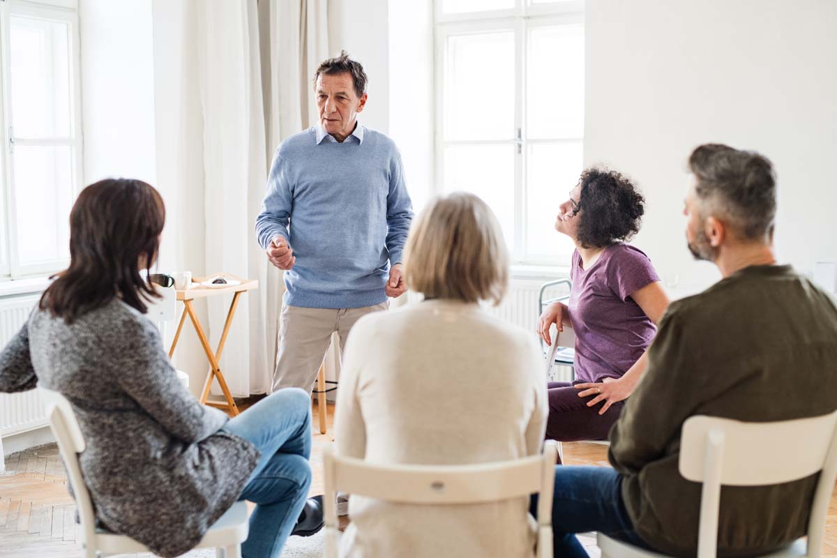 A man talking to other people during group therapy.