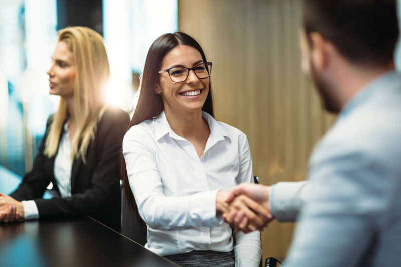 Young business woman shaking hands with coworker